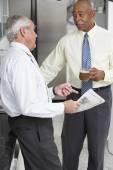 Two senior businessmen talking in break room — Stock Photo