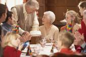 Grandmother getting her birthday cake at the table with family — Stock Photo