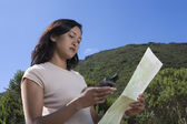 Woman reading map and gaps in forest — Stock Photo