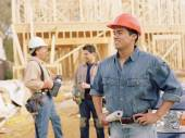 Manual worker holding blueprints on site — Stockfoto