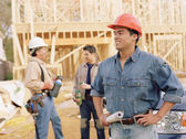 Manual worker holding blueprints on site — Stock Photo