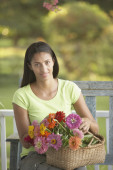 African woman sitting with basket of flowers — Stock Photo