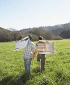 Couple carrying their lawn chairs across green meadow — Stock Photo