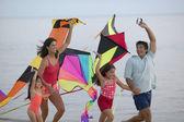 Family flying kite on beach — Stock Photo
