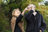Senior woman pointing while senior man takes photograph outdoors — Foto de Stock