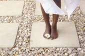 African American woman's bare feet with flower — Stock Photo
