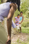 African sister and brother playing with mother in park — Stock Photo
