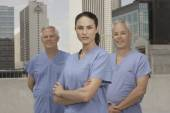 Doctors standing on roof in urban setting — Stock Photo