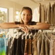 African woman leaning on rack at clothing store — Stock Photo #52040257