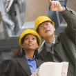 Two businesspeople in hard hats holding blueprints — Stock Photo #52040333