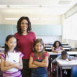 Female teacher and students smiling in classroom — Stok fotoğraf #52040339