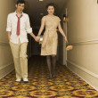 Young coupled dressed up walking down hotel hallway — Stock Photo #52041207