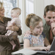 Father helping daughter use laptop while mother holds baby — Stock Photo #52041249