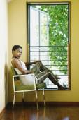 African woman sitting next to window — Stock fotografie