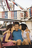 Women kissing either of a man's cheeks on a roller coaster — Stock Photo