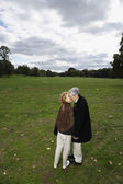 Senior couple kissing in open meadow — Stock Photo