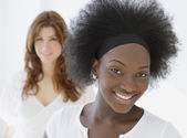 African woman smiling with friend in background — Stock Photo