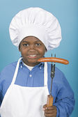 African boy in chef's hat holding hot dog — Foto Stock