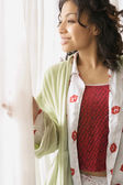 African woman in pajamas looking out window — Photo