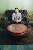 Pacific Islander man on sofa next to carved table — Stock Photo