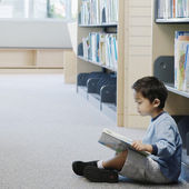 Boy reading in library — Stock Photo