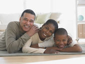 African family laying on livingroom rug smiling — Stockfoto