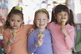 Group of young girls eating ice cream cones — Stock Photo