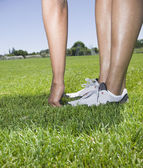 African person touching toes in grass — Stock Photo