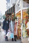 Two women on th sidewalk shopping — Stock Photo