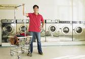 Asian man in laundromat — Stock Photo