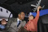 Father and son playing with an airplane in a limo — Stock Photo