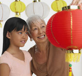 Asian grandmother and granddaughter looking at paper lanterns — Foto Stock