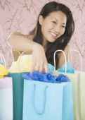 Young Asian woman smiling with shopping bags — Stock Photo