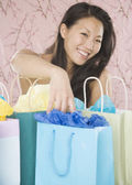 Young Asian woman smiling with shopping bags — Foto Stock