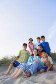 Hispanic family sitting on beach — Stock Photo