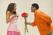Young man giving girlfriend a bunch of flowers — Stock Photo