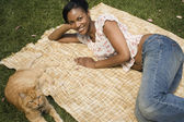 African woman laying on blanket in grass with cat — Stock Photo
