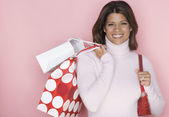 Woman with gift bags over shoulder — Stock Photo