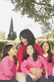 Asian mother with three young daughters laughing outdoors — Stock Photo