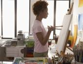Female artist looking at canvas — Stock Photo