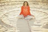 Woman sitting cross-legged in the middle of a meditation labyrinth — Stock Photo