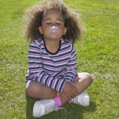 Young African girl sitting in grass blowing bubble gum — Stock Photo