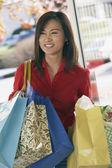 Asian woman carrying shopping bags — Stockfoto