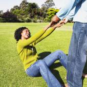 African man helping girlfriend up off grass — Stock Photo