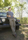 Young man leaning on jeep in woods — Stock Photo