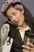 Hispanic zakenvrouw met krulspelden in haar holding koffiemok en krant en het gebruik van mobiele telefoon — Stockfoto