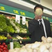 Unternehmer holding melone vor seinem gesicht im supermarkt — Stockfoto