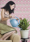 Young woman watering house plant — Stock Photo