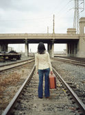 Young woman walking on train tracks — Stock Photo
