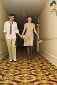 Young coupled dressed up walking down hotel hallway — Stock Photo
